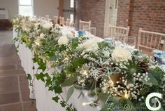 Winter top table arrangement of roses, lisianthus and gypsophila with pine cones, spruce branches and eucalyptus