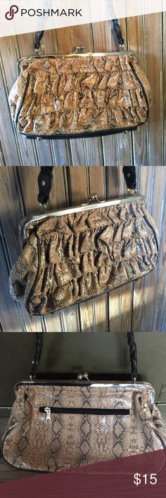 Black & Tan Snakeskin Ruffled purse Super Cute💕 Carried just a couple times-great condition! This is UNIQUE! A tan/lighter brown & black snakeskin design pattern w/a ruffled look in the front, a black faux leather braided strap & bottom- w/silver feet & hardware. This clasps shut & has a roomy inside w/a couple smaller pockets & 1 zippered pocket! This also has a zippered pocket on the back of the outside! This is unique & stylish!! A medium shoulder bag this measures approx. 11.5x7 in…