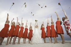 Photo of a bride and her bridesmaids throwing roses into the air on the beach at a destination wedding in The Bahamas which was photographed by Stop Motion Productions, a Bahamas Wedding Photographer.