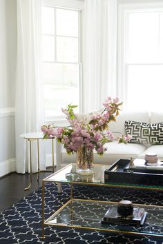 Fresh flowers play off the living room's light, airy palette to create a refreshing vignette on the coffee table.   - ELLEDecor.com