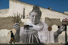 En la calle Taxdirt se encuentra el fotomural de Juana la del Pipa, que aparenta sostener unas ramas que sobresalen del edificio.