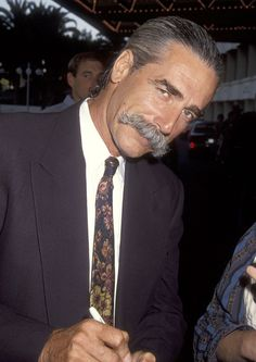 Sam Elliott. Tall, thin, wiry, he is the classic picture of the American cowboy. Elliott began his acting career on the stage and his film debut was in Butch Cassidy and the Sundance Kid. Over the years there would be few opportunities to act in feature westerns he mostly has been on the small screen though we all loved him in The Big Lebowski. His Voice knocks me out.