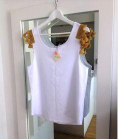 White vest with tasseled shoulder details - summarize in style!