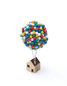 Whether you need to pin up a pin-up, or drop a pin on a map, the Balloon  Pin House provides an enchanting place for you to store your map or  noticeboard pins.  300 individual pins float above a tiny rooftop in a miniature balloon  cluster.  Arrange your balloons by simply pressing each pin in to a solid cork ball  core. Each ball is securely mounted upon three robust steel pins protruding  from a tiny brass tubed chimney.The small wooden plywood house base can be  stood upright on flat…