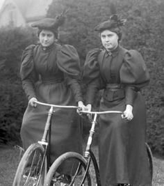 Two young ladies out for a bicycle ride in elegant attire.