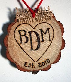 """3 Letter Monogram Initial Heart Personalized Handmade Christmas Ornament Rustic Engraved Wood Tree Slice. Beautifully rustic, eco-friendly tree slice Christmas or holiday ornament, engraved by hand with 3 intitals of your choice and topped with a cute burlap bow and red yarn hanger. Each monogrammed tree slice measures approx 3"""" to 4"""" in diameter, as they are an all natural product, there will be slight variances. The 3 initials are hand engraved inside a rustic heart and est.year is..."""