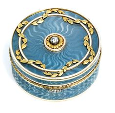 "A Jewelled Two-Colour Gold Mounted Guilloché Enamel Pill-Box Marked Fabergé, with the workmaster's mark of Feodor Afanassiev, St Petersburg, 1908-1917, Circular, the body enamelled in translucent grey over a wavy guilloché ground within opaque white enamel and bright-cut borders, the hinged cover centering a gold-mounted rose-cut diamond, within a chased gold foliate garland, the laurel chased border with diamond set thumb-piece. Diameter 1-5/8""."