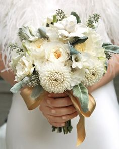 Cream colored bouquet tied with a gold sash