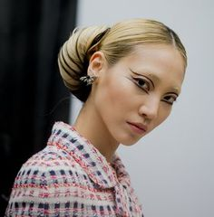 Go Graphic - Amid Chanel's structured Zen backdrop, traditional flicks of winged black eyeliner were replaced by stylized delineations that mirrored the sculptural updos.