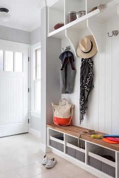 White mudroom features shelves over open mudroom lockers lined with hooks as well as a built-in bench fitted with cubbies filled with gray woven bins.
