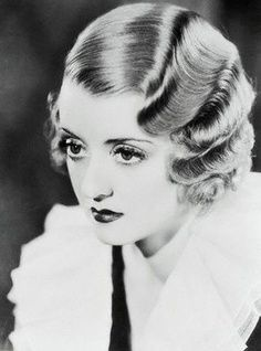 Marcel Wave - Hair style parted to the side in which hot tongs were used to curl the hair. A popular style for women's hair in the 1920s, in competition with the bob