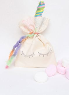 These Calico bags are perfect for creating the cutest unicorn themed party favours for your party guests. Set of 10. Why not pop a long swirl lolly pop in each bag for the unicorns horn?!  Please note, the fluffy rainbow wool featured in the main photo is out of stock. I have a thinner, but still gorgeous, rainbow wool tie that will come with the bags. Please refer to last photo.  *Hand stamped *10cm Wide x 16cm High  *Rainbow wool tie included for each bag. All bags are made upon order…