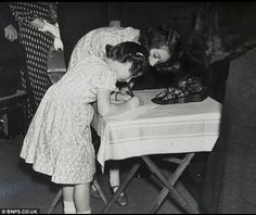 Princess Elizabeth helps Margaret to sign the tiny autograph book from a Doll's house
