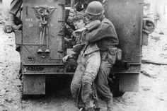 An American infantryman picks up a wounded German soldier on the road to St. Lo France and helps him into a half-track. The German was abandoned by his own troops after being wounded. 20 June 1944.