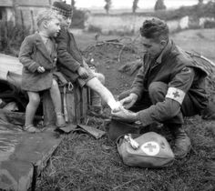 Royal Canadian Army Medical Corps (RCAMC) corporal W.J. Curtisbandages the burned leg of a French boy who wears the soldier's glengarry cap, while his young brother looks on. Between Colomby-sur-Thaon and Villons-les-Buissons, Normandy, France.19 June 1944.