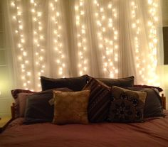 DIY lights headboard! Hang string lights from command hooks and use a cheap curtain rod and $6 curtains from IKEA over the lights.