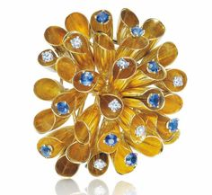 GRIMA A Gold, Sapphire and Diamond Brooch, 1960's  Designed as a stylized foliate spray of polished gold trumpet leaves, enhanced by circular-cut sapphires and diamonds, mounted in 18K yellow gold, length 2 1/4 inches.