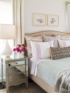 Layers of neutrals, such as the barely gray walls, oatmeal bed, and chocolate accent pillows, wrap this bedroom in serene comfort. A mirrored nightstand and hints of purple in the bedding add subtle flair./