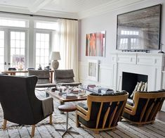 The fireplace steals the show in this living room, thanks to a large, statement-making painting placed on the mantel. A collection of mismatched furniture pieces creates a semicircular arrangement in front of the fireplace, w