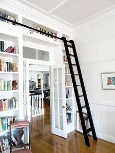 white built-in bookcases with black library ladder / sfgirlbybay