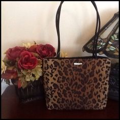Nine West Animal Print Handbag This animal print handbag is a soft body with black nylon handles. The handles length is 27 1/2 inches the body is 13 1/2 inches wide the height is 10 inches. There is three compartments the center one is a zip. One side had a zipper and the other compartment does not. Nine West Bags