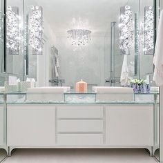Stunning bathroom with glass-top double vanity accented with white vessel sink and wall-mounted faucets paired with glass bubbles sconces on ceiling height mirror.