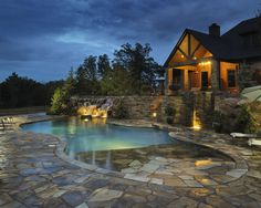 Elaborate pool with dry laid stone retaining walls, flagstone patios and beach entry, with natural boulder waterfall.
