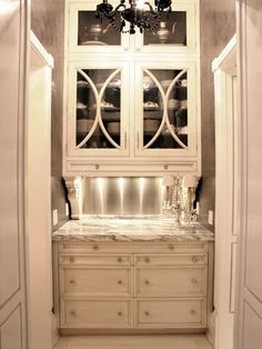 Chic butler's pantry design with calcutta marble countertop, white glass-front cabinets, stainless steel backsplash and glossy black crystal chandelier. Interior Exterior, Interior Design, Interior Modern, Glass Front Cabinets, Upper Cabinets, Pantry Cabinets, White Cabinets, Cream Cabinets, Pantry Cupboard