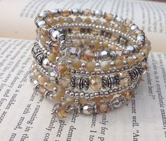 A 7 coil memory wire wrap bracelet featuring smooth 3mm smooth natural mother of pearl beads, matching 4X6mm faceted peachy/tan glass crystals, and 4mm faceted glass cube crystals. Accented with a variety of Tibetan silver spacer beads. Finished with a wire wrapped 4X6mm crystal on