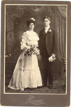 "+~+~ Antique Photograph ~+~+  Wedding Portrait of couple, Chicago c. 1890. Her gown is of white, sheer cotton and its bodice is made in the fashionable ""pouter pidgeon"" style of the day. The skirt is trimmed with a large flounce of alternating strips of fabric and lace. Instead of a veil, she wears a white bow. Her narrow waist is encircled by a wide satin ribbon, and its streamers hang down her back. She carries a lovely bouquet of roses and ferns tied up with a wide ribbon."