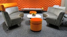Intima Public Modular with headrest and shelf options along with Nios Occasional Table with Corian top and orange powdercoat base & Islands round seats