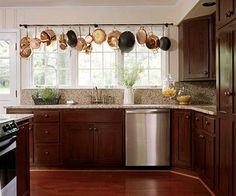 Love the function of the pot rack doubling as a window valance.  And who would not love to have that many windows in your kitchen!!