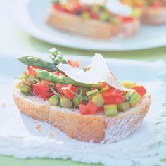 Der Italo-Party-Snack: köstliche Bruschetta (italienische Schnittchen) belegt mit gebratenem grünen Spargel, Basilikum und Tomaten.