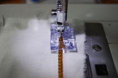 Un pied pour les cordons et perles. Il a en son milieu un petit canal qui permet de coincer et guider un petit cordon ou des petites perles sur un fil et aussi de créer des passepoils.