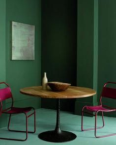 Dark green walls make a moody background for plum powdercoat steel dining chairs and a walnut wood slab topped pedestal tulip table.