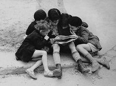 Children Reading a newspaper. Paris.