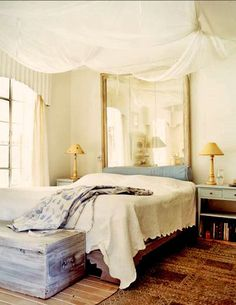 Romantic bedroom w/ ceiling-suspended mosquito-net canopy and mirror as headboard