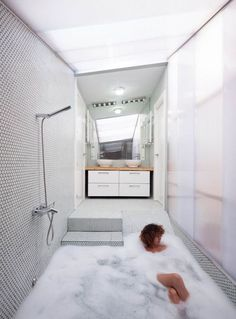 O banheiro desnivelado deu espaço para uma banheira inusitada, que cobre o piso da área do chuveiro.