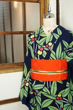 こっくりと深い黒に近い濃紺色の地に、緑美しい葉と赤と黄色の彩り鮮やかな実の模様が染め出された注染レトロ浴衣です。