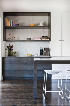 marble counters, blackened wood & white cabinetry with open shelving in the kitchen