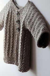 Demne is a first size baby cardigan worked from cuff to cuff in one piece. The seed stitch bands at hem, wrist, and neck, and the seed stitch button and buttonhole bands, are all knitted-in. The neck is wide for ease of dressing your little one.