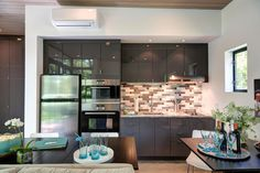 In this small and modern kitchen, dark glossy cabinets stand out against the white walls and stainless steel appliances, and multiple dining tables makes sure there is enough space for everyone to dine at.