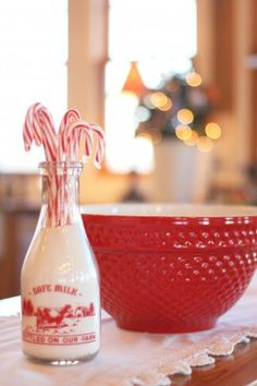 "Farmhouse Christmas. Vintage milk bottle filled with ""milk"" (actually salt)...candy canes spilling out the top. A big red bowl ready to make Christmas cookies!"