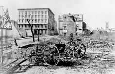 The ruins of Mills House and nearby buildings in Charleston, with a shell-damaged carriage and the remains of a brick chimney in the foreground. 1865.