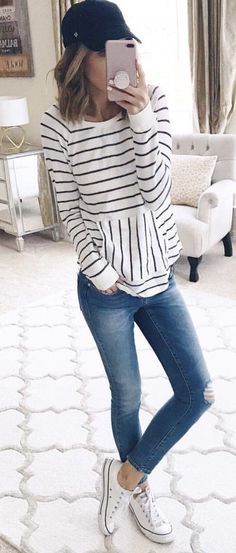 #spring #outfits woman holding smartphone wearing long-sleeved shirt and jeans. Pic by @kateireneblue