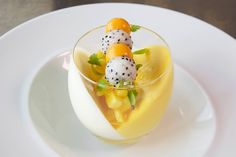 Dessert presentation ideas. Tilt glass, pour in one flavour mousse / sorbet and freeze on the tilt. Fill with a second selection and tilt in the opposite direction. Fill bottom with selected fruit. Balance a teeny 'kebab' of skewered balls of fruit (in this case dragon fruit and mango).