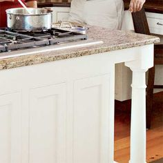 A granite topped kitchen island with turned legs features a cooktop and prep area