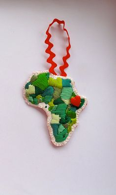 This embroidered ornament of Africa has been handmade in an array of green colors with a red heart button over the country of your choice- Please specify during checkout. It has been sewn onto a festive red felt backing with a red ribbon loop for hanging on the Christmas tree or