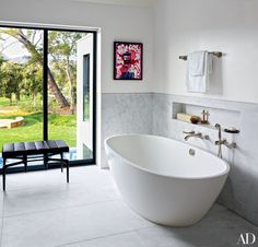 A work by Kenny Scharf adds punch to television producer Brian Grazer's marble-lined bath in his California home by Waldo Fernandez.