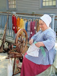 This older Amish woman, sits and spins to make the beautiful scarves like those hanging behind her...
